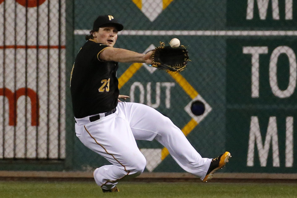 Photo - Pittsburgh Pirates right fielder Travis Snider slides to make the catch on a fly ball hit by Milwaukee Brewers' Jonathan Lucroy during the ninth inning of a baseball game in Pittsburgh, Thursday, April 17, 2014. The Pirates won 11-2. (AP Photo/Gene J. Puskar)