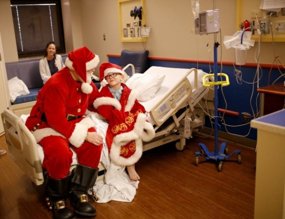 Photo -  Logan Harrison, 7,  wears Santa's coat during a visit Christmas Eve at Integris Children´s at Baptist Medical Center.   [Sarah Phipps/The Oklahoman]