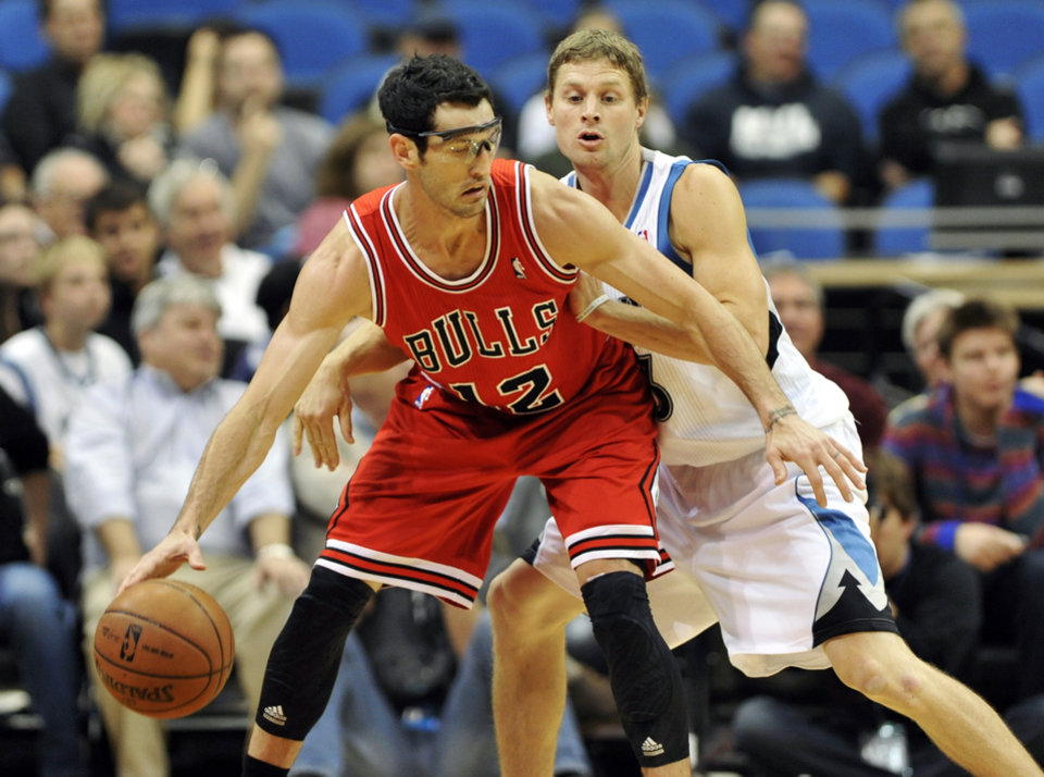 Chicago Bulls' Kirk Hinrich, left, is pressured by Minnesota Timberwolves' Luke Ridnour in the first half of an NBA preseason basketball game, Saturday, Oct. 13, 2012, in Minneapolis. (AP Photo/Jim Mone)
