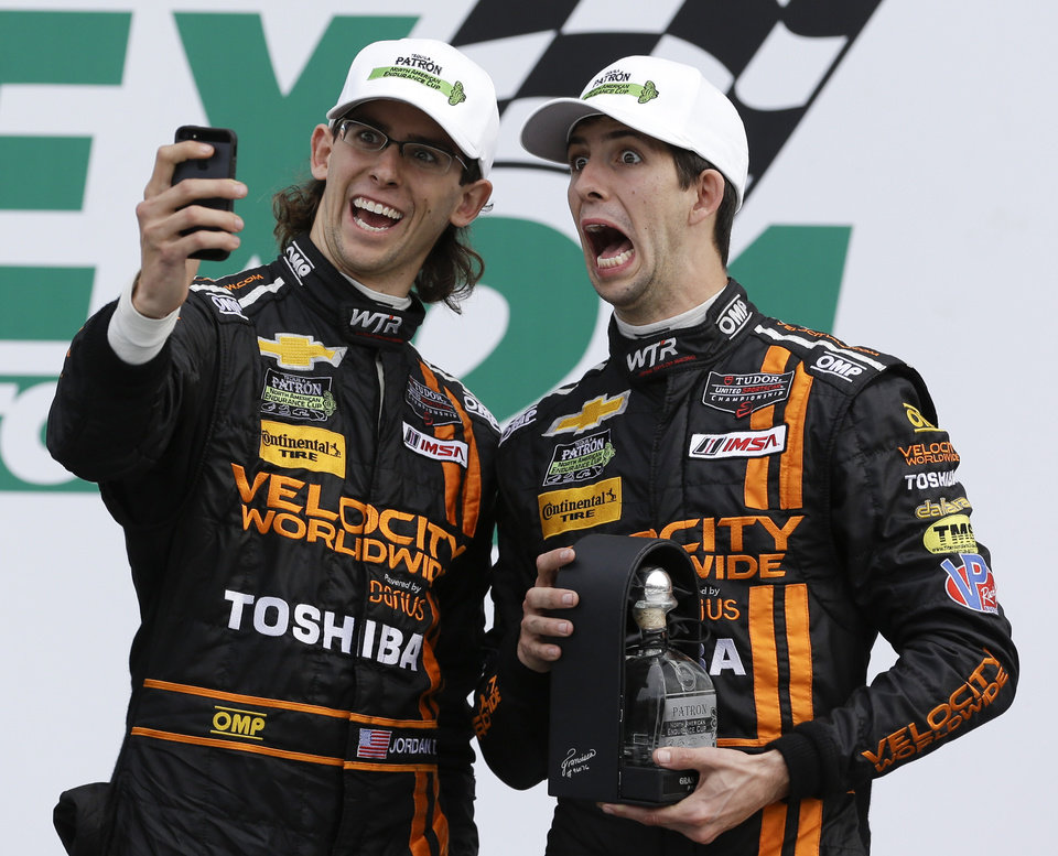 Photo - Jordan Taylor, left, and his brother Ricky Taylor take a photo of themselves in Victory Lane after they placed second in the IMSA Series Rolex 24 hour auto race at Daytona International Speedway in Daytona Beach, Fla., Sunday, Jan. 26, 2014.(AP Photo/John Raoux)
