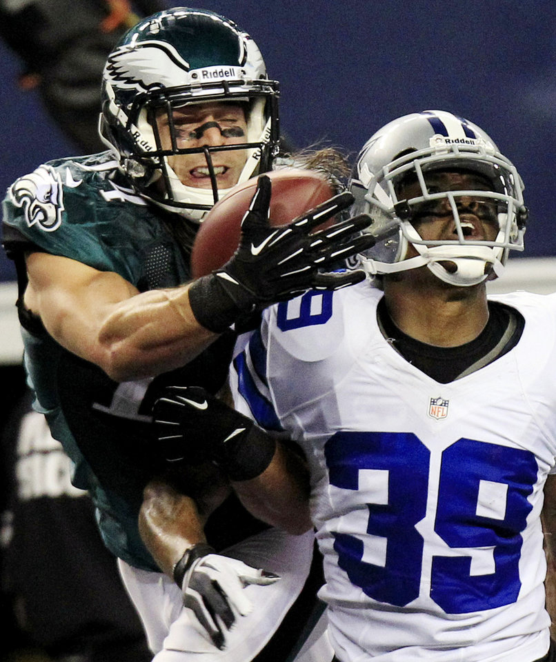 Photo - FILE - In this Dec. 2, 2012, file photo, Philadelphia Eagles wide receiver Riley Cooper (14) makes a touchdown reception as Dallas Cowboys cornerback Brandon Carr (39) defends during an NFL football game in Arlington, Texas. Cooper has been fined by the team for making a racial slur at a Kenny Chesney concert that was caught on video, leading him to say he's