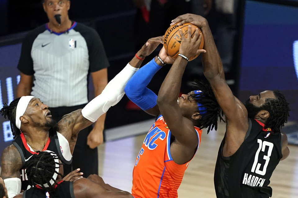 Photo - Oklahoma City Thunder's Luguentz Dort (5) goes up for a shot as Houston Rockets' James Harden (13) and Robert Covington, left, defend during the second half of an NBA basketball first round playoff game Saturday, Aug. 29, 2020, in Lake Buena Vista, Fla. (AP Photo/Ashley Landis)