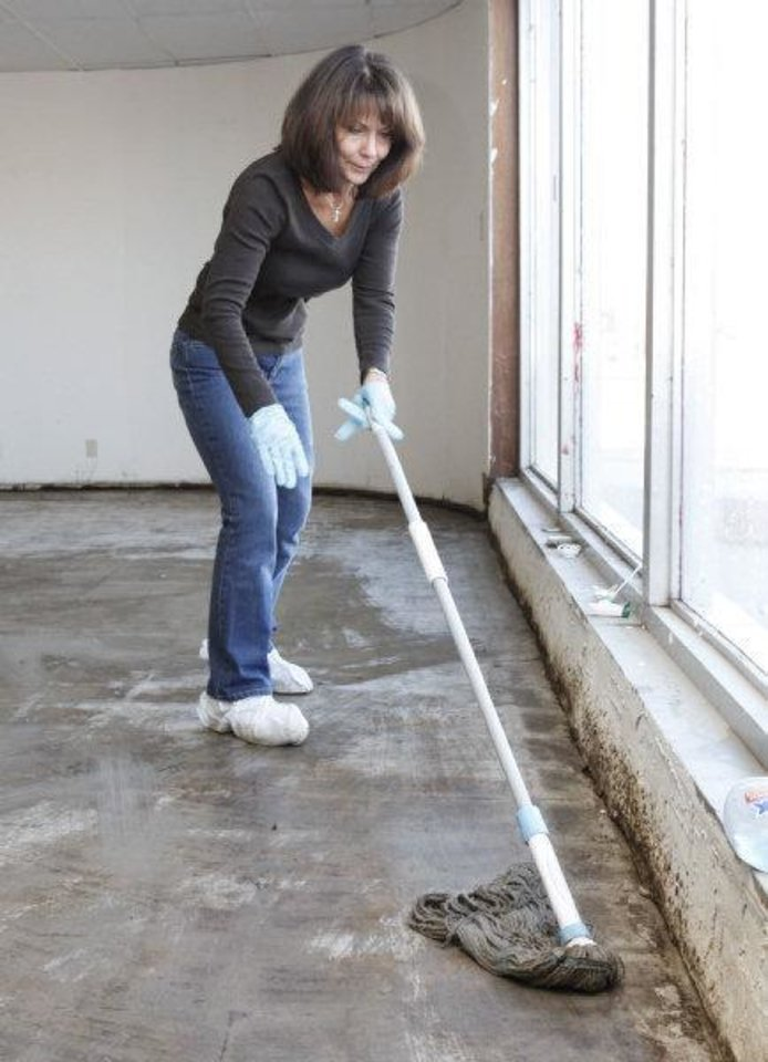 Dianna Herbert mops a floor Saturday as members of Southern Nazarene University's class of 1980 work to help Love Link Ministries Inc. prepare to move into a new building in downtown Oklahoma City. PHOTO BY PAUL HELLSTERN, THE OKLAHOMAN <strong>PAUL HELLSTERN</strong>