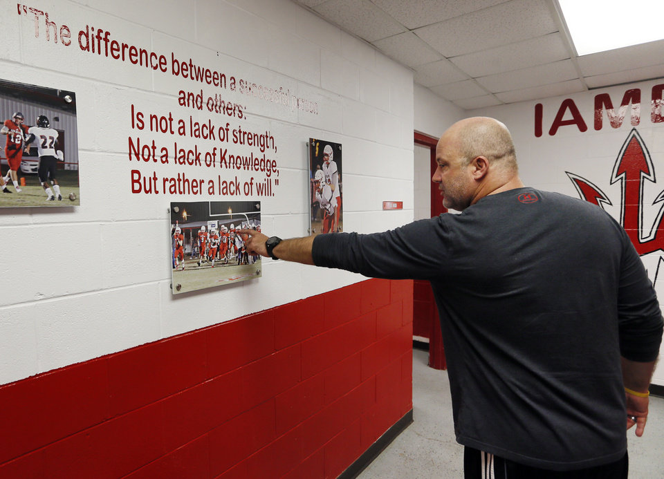"Photo -  Prague football coach Shannon Watford points out Emmanuel ""EJ"" Zenon, a 16-year-old player who was shot and killed in Oklahoma City, on Wednesday in a picture hanging inside the high school's athletics building in Prague. [Photo by Nate Billings, The Oklahoman]"