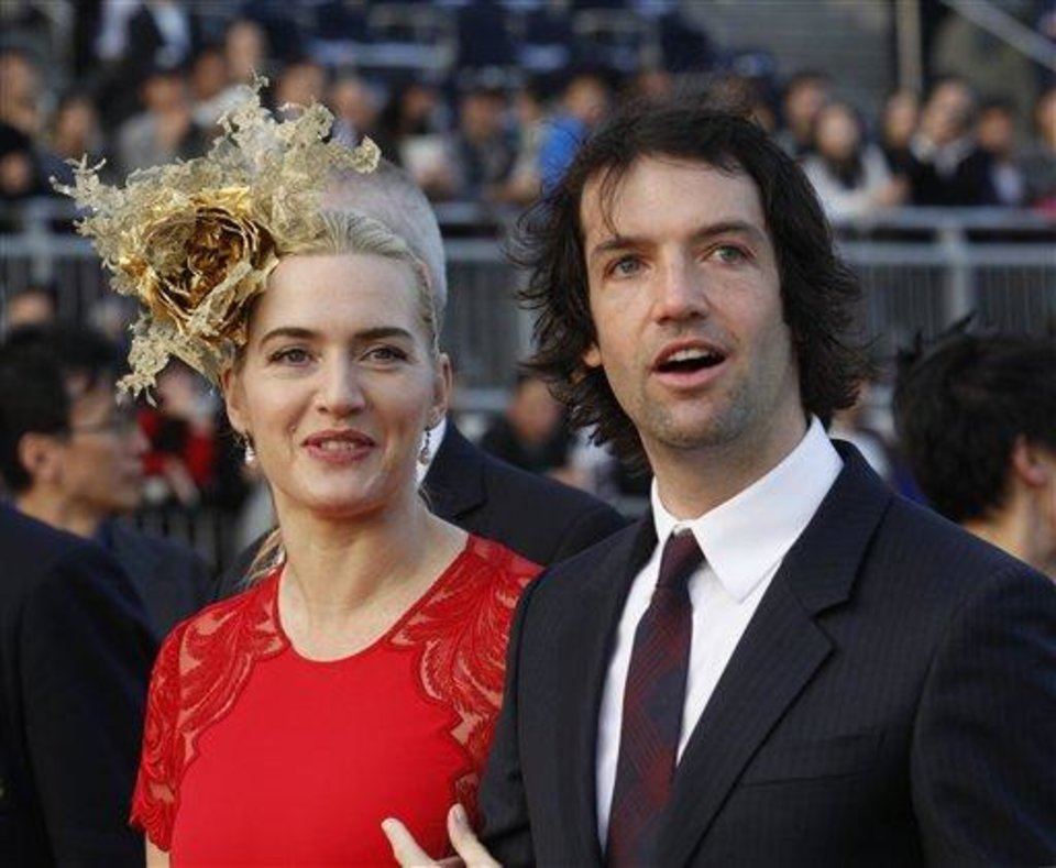 British actress Kate Winslet, left, arrives with her boyfriend Ned Rocknroll at the awards presentation of The Longines Hong Kong Cup horse race at the Shatin race track in Hong Kong, Sunday, Dec. 9, 2012. (AP Photo/Kin Cheung)