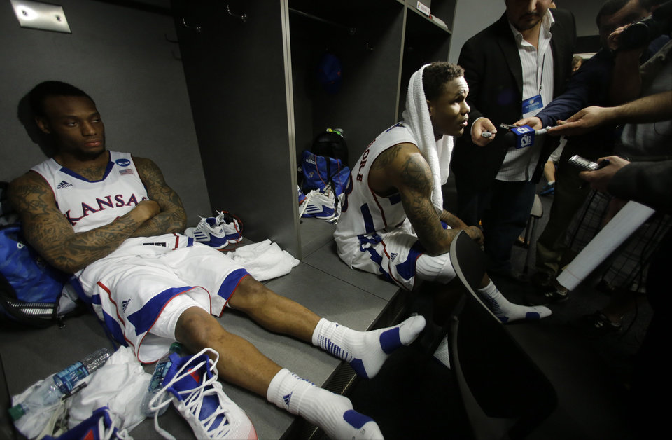 Photo - Kansas' Naadir Tharpe, left,  and Ben McLemore right react in the lockeroom after losing 87-85 to Michigan in overtime of a regional semifinal game in the NCAA college basketball tournament, Friday, March 29, 2013, in Arlington, Texas. (AP Photo/Tony Gutierrez)