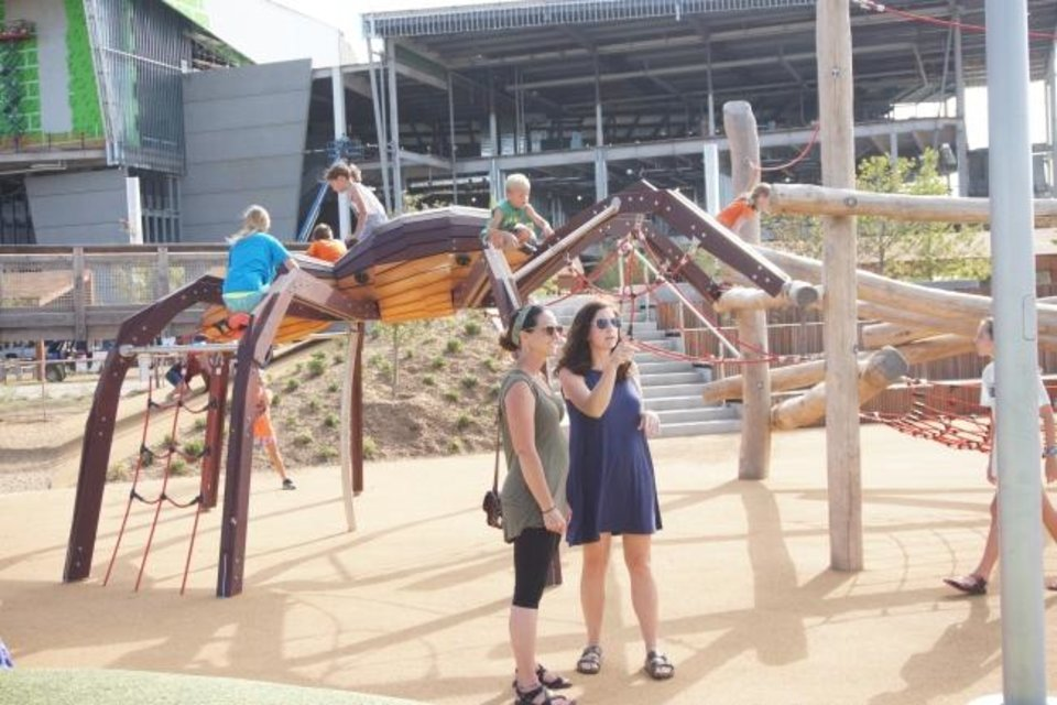 Photo -  Julie Kellogg, right, and Heather Green watch their children play Monday at Scissortail Park in downtown Oklahoma City. [Ben Felder/The Oklahoman]