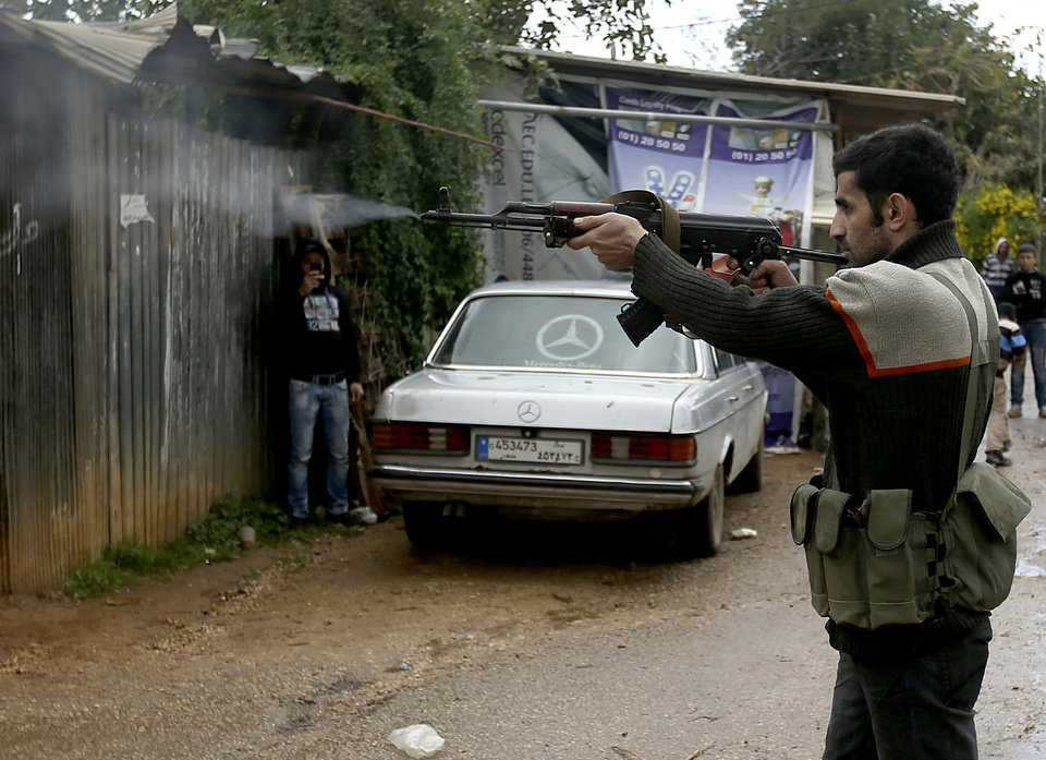Photo - A Sunni gunman fires his weapon during clashes that erupted between pro and anti-Syrian regime gunmen in the northern port city of Tripoli, Lebanon, Wednesday, Dec. 5, 2012. Gunmen loyal to opposite sides in neighboring Syria's civil war battled in the streets of northern Lebanon and the death toll from two days of fighting was at least five killed and 45 wounded, officials said. The fighting comes at a time of deep uncertainty in Syria, with rebels closing in on President Bashar Assad's seat of power in Damascus. (AP Photo/Hussein Malla)