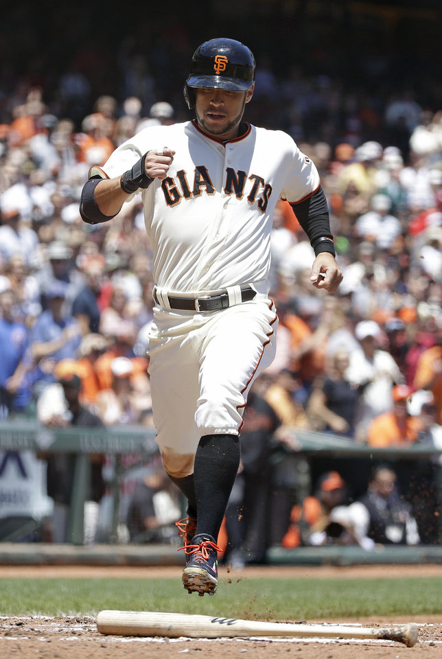 Photo - San Francisco Giants' Gregor Blanco crosses home plate to score the Giants' first run in the third inning of their baseball game against the St. Louis Cardinals Thursday, July 3, 2014, in San Francisco. Blanco scored after Madison Bumgarner singled a line drive to left field. (AP Photo/Eric Risberg)