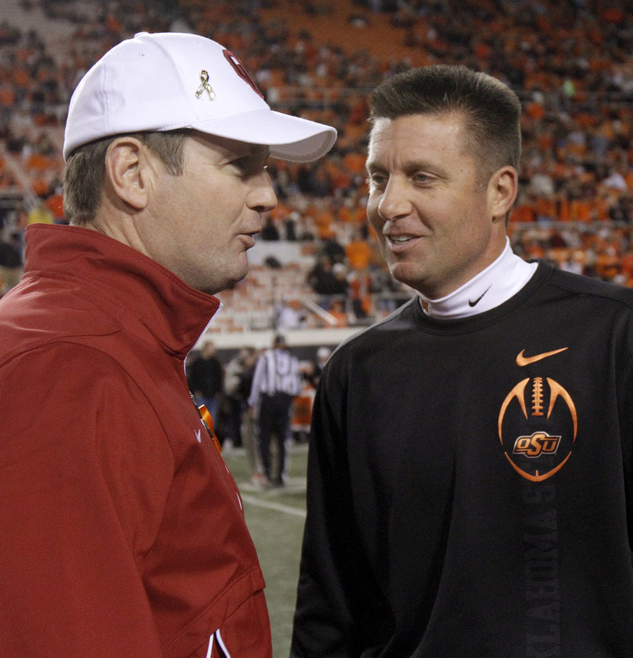 Oklahoma coach Bob Stoops and Oklahoma State coach Mike Gundy meet before the Bedlam college football game between the Oklahoma State University Cowboys (OSU) and the University of Oklahoma Sooners (OU) at Boone Pickens Stadium in Stillwater, Okla., Saturday, Dec. 3, 2011. Photo by Bryan Terry, The Oklahoman