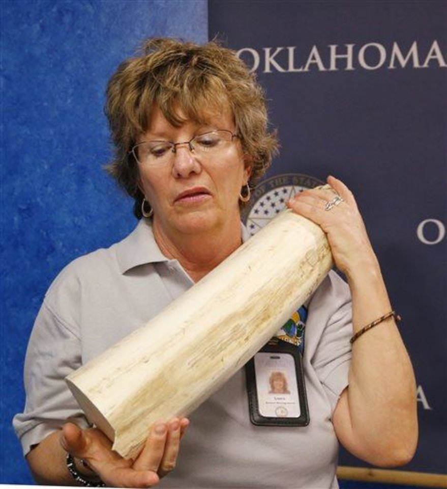 Photo -  Laura Bottaro, curator at the Oklahoma City Zoo, holds a 20-pound piece of ivory valued at more than $30,000 from the tusk of an Asian elephant, following a news conference Tuesday at the state Capitol in Oklahoma City. Democratic state Rep. Mike Shelton is sponsoring a bill that he says is designed to help curb illegal poaching of wildlife in Africa, where several species are threatened because of the black market ivory trade. AP Photo   Sue Ogrocki -  AP