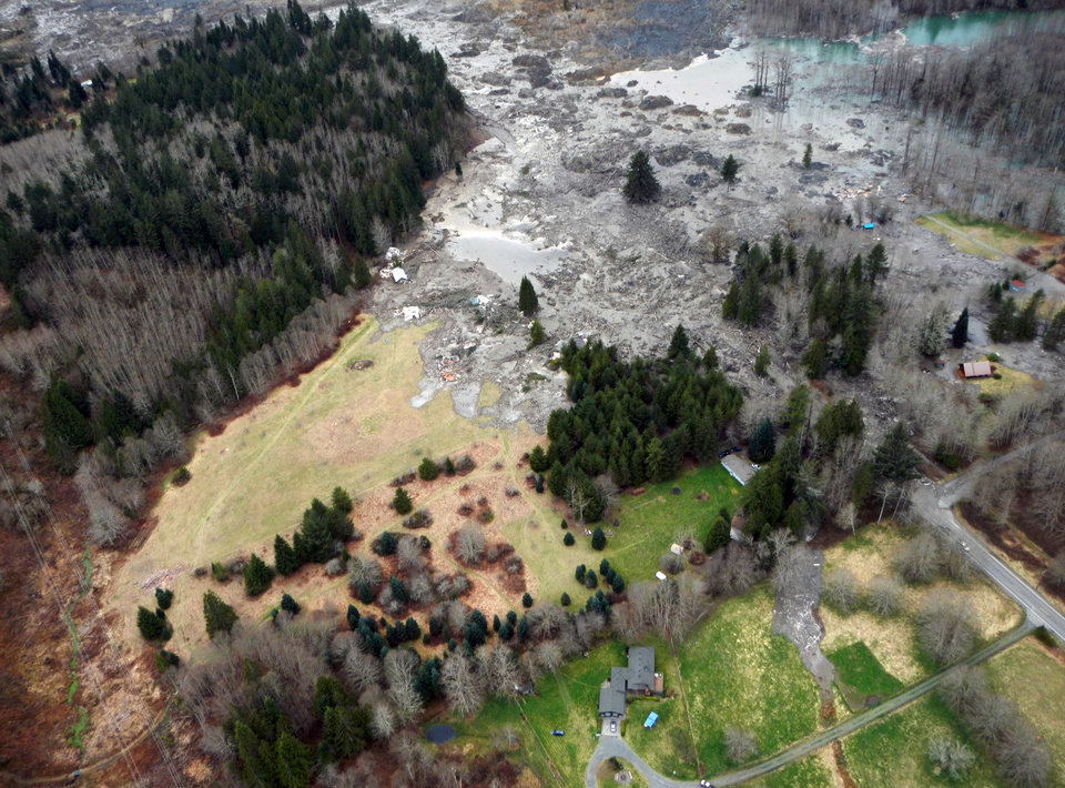 Photo - This March 23, 2014 photo, made available by the Washington State Dept of Transportation shows a view of the damage from Saturday's mudslide in Oso, Wash. At least eight people were killed in the 1-square-mile slide that hit in a rural area about 55 miles northeast of Seattle on Saturday. Several people also were critically injured, and about 30 homes were destroyed. (AP Photo/Washington State Dept of Transportation)