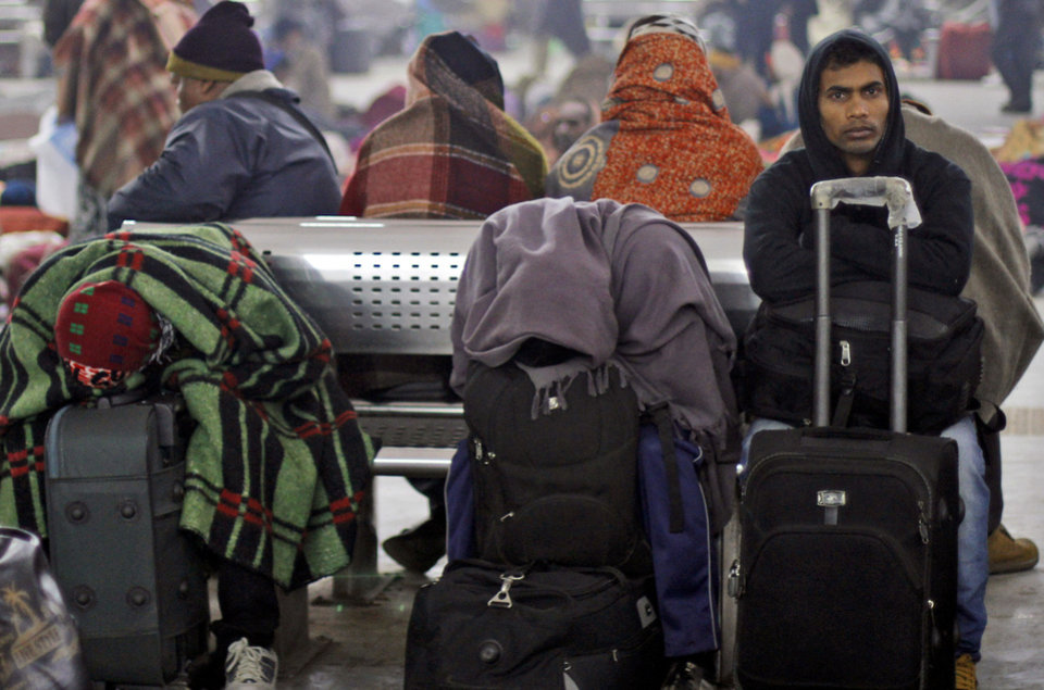Passengers rest their heads on their luggage as they wait for the arrival of a train at a railway station in Allahabad, India, Saturday, Dec. 29, 2012. North India continues to face extreme weather conditions with dense fog affecting flights and trains, according to local reports. (AP Photo/Rajesh Kumar Singh)
