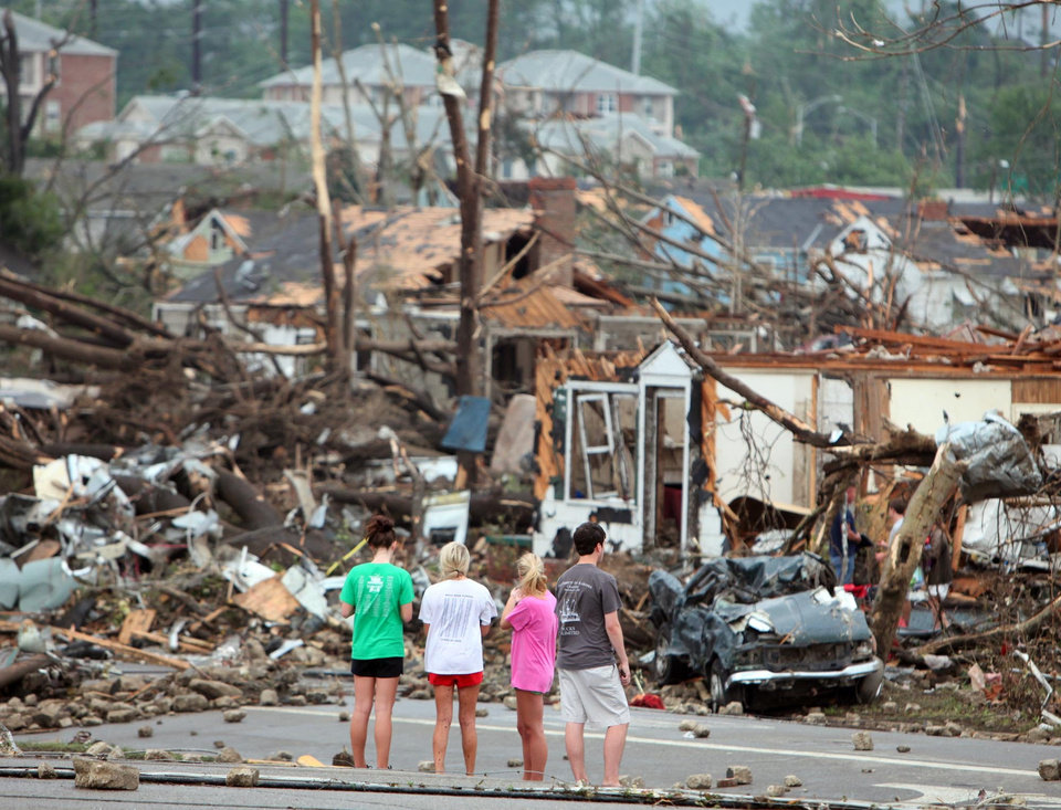 Photo - Bystanders look on at storm damage along 15th Street in Tuscaloosa, Ala., Wednesday, April 27, 2011. A strong tornado moved through the city Wednesday afternoon. (AP Photo/The Tuscaloosa News, Dusty Compton)