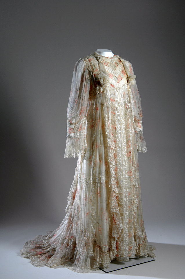 Photo - This image released by The Museum at FIT shows a tea gown in off-white silk crimped chiffon with red and green carnation print, pieced with bands of lace  and lace-trimmed sleeves with a china silk underdress.  From a 1770 corset to a 2014 bra-and-panty set in lacy stretch silk, the Museum at the Fashion Institute of Technology has taken on lingerie and ladies foundation garments as the focus of a new exhibition. In about 70 pieces,