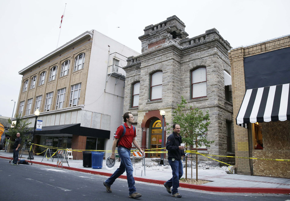 Photo - Structural engineers Steve Heyne, left, and Chris Jonas, right, walk past the earthquake-damaged Goodman Library, Monday, Aug. 25, 2014, in Napa, Calif. The pair were making a number of inspections in the area. The San Francisco Bay Area's strongest earthquake in 25 years struck the heart of California's wine country early Sunday, igniting gas-fed fires, damaging some of the region's famed wineries and historic buildings, and sending dozens of people to hospitals. (AP Photo/Eric Risberg)