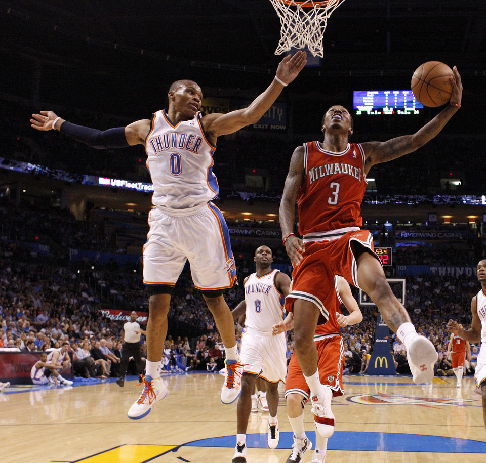 Photo - Milwaukee's Brandon Jennings (3) goes to the basket beside Oklahoma City's Russell Westbrook (0) during the NBA basketball game between the Oklahoma City Thunder and the Milwaukee Bucks at the Oklahoma City Arena, Wednesday, April 13, 2011. Photo by Bryan Terry, The Oklahoman