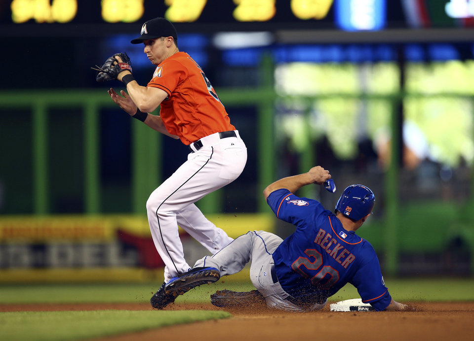 Photo - New York Mets' Anthony Recker (20) is safe at second as Miami Marlins' Ed Lucas tries to make a play during the fourth inning of a baseball game in Miami, Sunday, June 22, 2014.  (AP Photo/J Pat Carter)