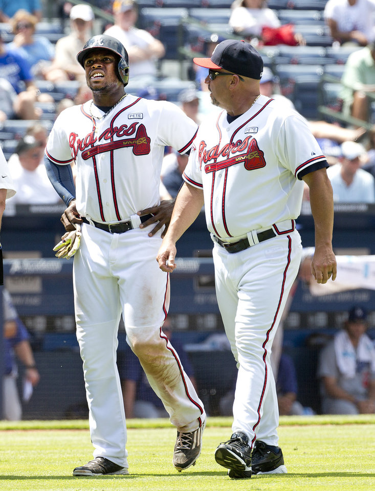Photo - Atlanta Braves left fielder Justin Upton (8) walks off the field with manager Fredi Gonzalez, right, after being injured sliding into third base in the eighth inning of a baseball game against the Los Angeles Dodgers Thursday, Aug. 14, 2014, in Atlanta. Los Angeles won 6-4. (AP Photo/John Bazemore)