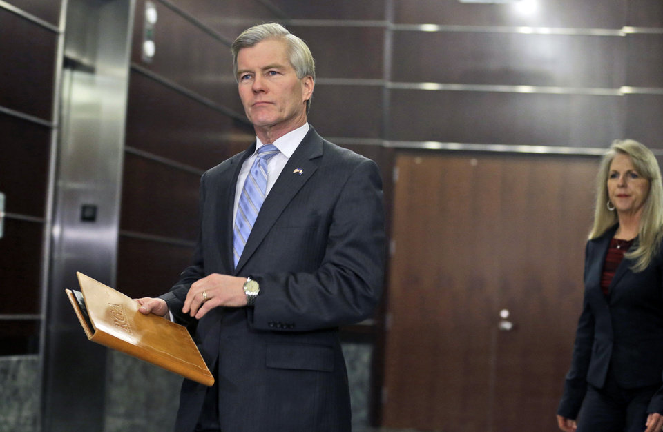 Photo - Former Virginia Gov. Bob McDonnell arrives to make a statement followed by his wife, Maureen, in Richmond, Va., Tuesday, Jan. 21, 2014.  McDonnell and his wife were indicted Tuesday on corruption charges after a monthslong federal investigation into gifts the Republican received from a political donor.  (AP Photo/Steve Helber)