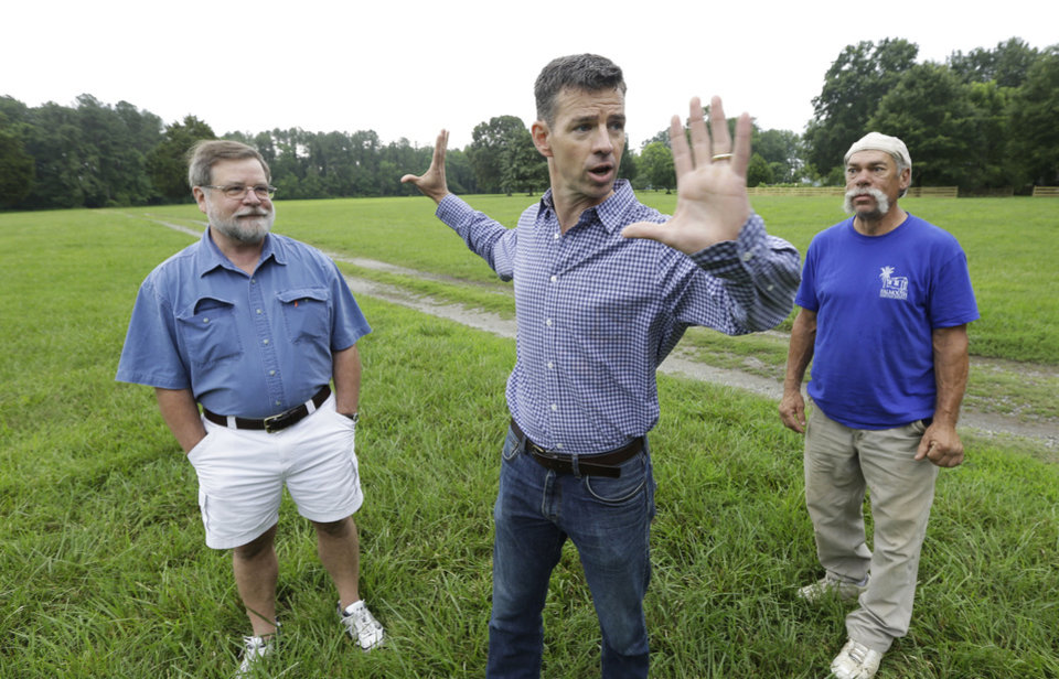 Photo - Martin Gallivan, College of William professor, center, gestures as Pamunkey Indian Jeff Brown, right, and  Randolph Turner, retired state archaeologist, left, listen during a tour of a farm field overlooking the York River in  Gloucester, Va., Monday, June 17, 2013. The field is known to many in Virginia as the place where Pocahontas interceded to rescue Capt. John Smith from her powerful father, Powhatan, who ruled a vast empire in 1607  in (AP Photo/Steve Helber)