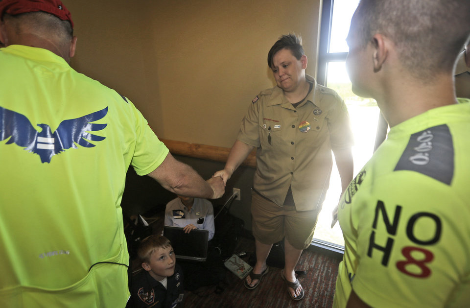 Photo - Former Boys Scout leader Jennifer Tyrrell, center, is greeted as her son and current Boy Scout Cruz Burns, 8, bottom, looks on during the Equal Scouting Summit being held near where the Boy Scouts of America are holding their annual meeting Wednesday, May 22, 2013, in Grapevine, Texas. Delegates to the Boys Scouts of America meeting are expected to address a proposal to allow gay scouts into the organization. (AP Photo/LM Otero)