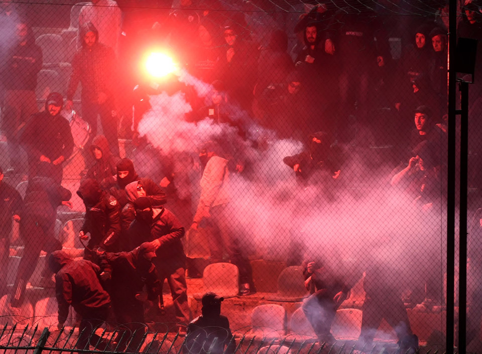 Photo - PAOK fans throw flares at Panathinaikos supporters shortly before the start of the Greek championship play-off match between their teams at Apostolos Nikolaidis stadium in Athens, Sunday, May 4, 2014. (AP Photo/InTime Sports) GREECE OUT