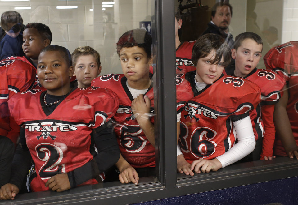 Photo - Members of the Moore Pirates look through a window to catch a glimpse of Bill Cowher as he talks with their parents at a clinic at Southmoore High school for two teams from the Oklahoma Elite Football League Wednesday, November 20, 2013. Photo by Doug Hoke, The Oklahoman