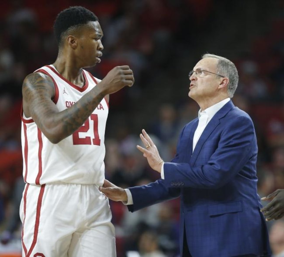 Photo -  Oklahoma coach Lon Kruger, right, talks with Kristian Doolittle during a timeout on Saturday in Norman. The Sooners beat Kansas State 66-61 to start Big 12 play. [Bryan Terry/The Oklahoman]