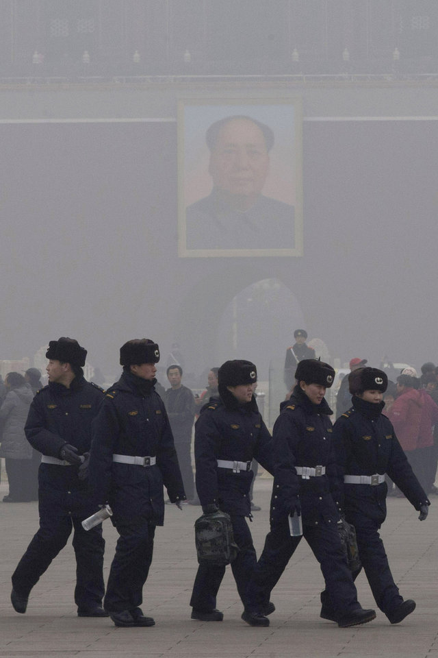 Photo - Chinese security personnel march in thick haze near the portrait of former Chinese leader Mao Zedong in Beijing Tuesday, Jan. 29, 2013. Extremely high pollution levels shrouded eastern China for the second time in about two weeks Tuesday, forcing airlines in Beijing and elsewhere to cancel flights because of poor visibility and prompting government warnings for residents to stay indoors. (AP Photo/Ng Han Guan)