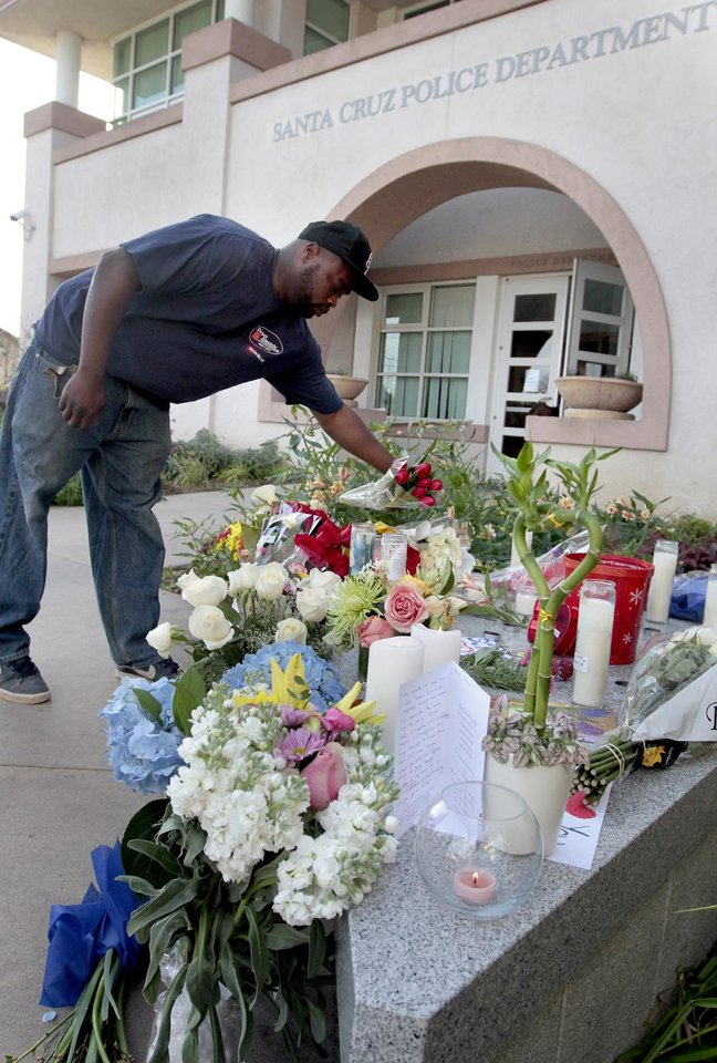 Passerby William Elmore lays a bouquet of flowers at the memorial to detectives Elizabeth Butler and Loran 'Butch' Baker at Santa Cruz Police Headquarters in Santa Cruz, Calif., Wednesday, Feb. 27, 2013. The detectives, responding to a sexual assault report Tuesday afternoon, were killed at the doorstep of a suspect who was chased down and killed half an hour later. (AP Photo/Santa Cruz Sentinel, Shmuel Thaler)