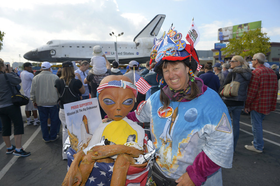 Vivianne Robinson Crowds poses in front of the Space Shuttle Endeavour before it is moved along city streets, Friday, Oct. 12, 2012, in Los Angeles. Endeavour's 12-mile road trip kicked off shortly before midnight Thursday as it moved from its Los Angeles International Airport hangar en route to the California Science Center, its ultimate destination, said Benjamin Scheier of the center. (AP Photo/Mark J. Terrill)
