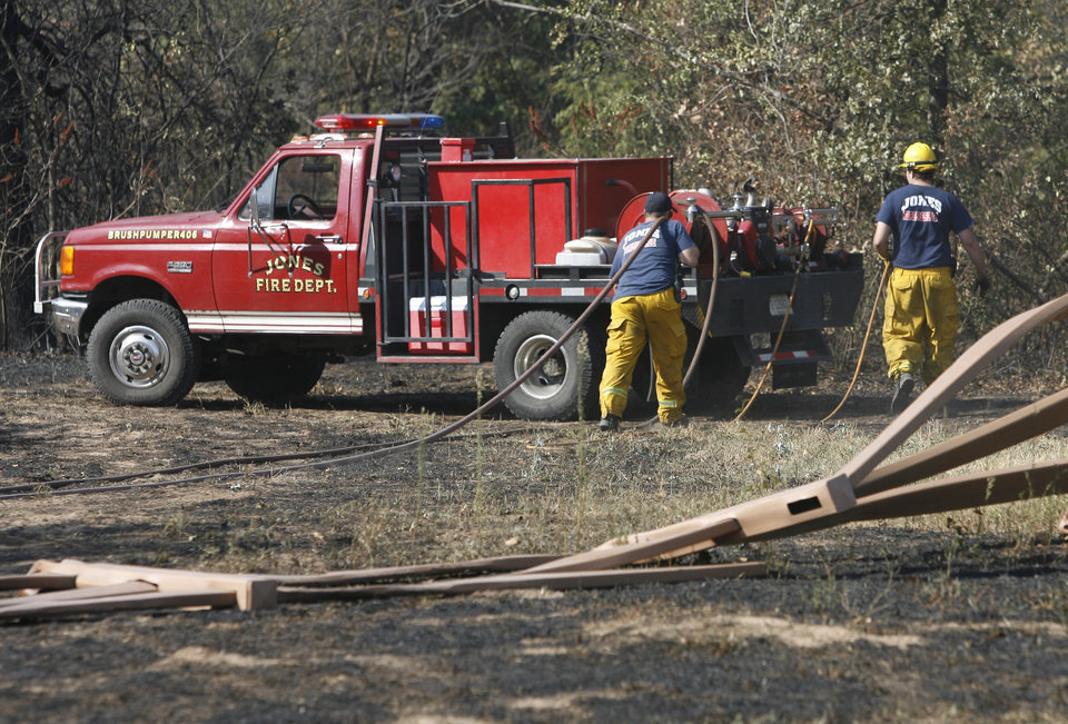 Photo - Jones firefighters spray hot spots near Britton road and Prosper drive after wildfires swept through the area in Oklahoma City , Wednesday, August 31, 2011. Photo by Steve Gooch, The Oklahoman