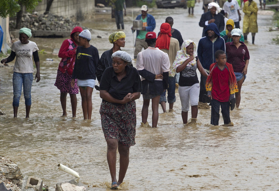 Photo -   In this photo released by the U.N. mission in Haiti, MINUSTAH, residents leave their flooded homes in a low lying area affected by Tropical Storm Isaac in Port-au-Prince, Haiti, Saturday, Aug. 25, 2012. Tropical Storm Isaac swept across Haiti's southern peninsula early Saturday, dousing a capital city prone to flooding and adding to the misery of a poor nation still trying to recover from the 2010 earthquake. (AP Photo/MINUSTAH, Logan Abassi)