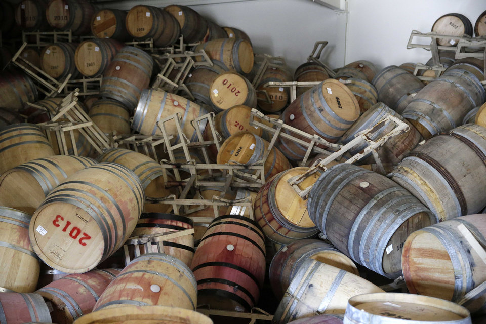 Photo - Barrels filled with Cabernet Sauvignon are toppled on one another following an earthquake at the B.R. Cohn Winery barrel storage facility Sunday, Aug. 24, 2014, in Napa, Calif. Winemakers in California's storied Napa Valley woke up to thousands of broken bottles, barrels and gallons of ruined wine as a result of Sunday's earthquake. (AP Photo/Eric Risberg)