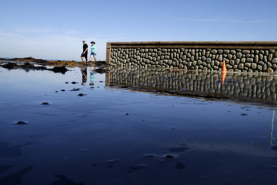 Photo - Two people walk along a partially flooded street where it meets the beach after higher than average tides caused minor flooding, Tuesday, Oct. 27, 2015, in San Diego. The so-called