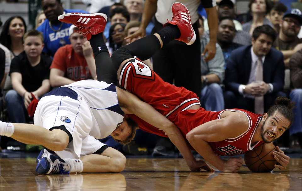 Photo - Chicago Bulls center Joakim Noah, right, tumbles over Dallas Mavericks forward Dirk Nowitzki (41), of Germany, to recover a loose ball during the second half of an NBA basketball game on Friday, Feb. 28, 2014, in Dallas. Chicago won 100-91. (AP Photo/John F. Rhodes)
