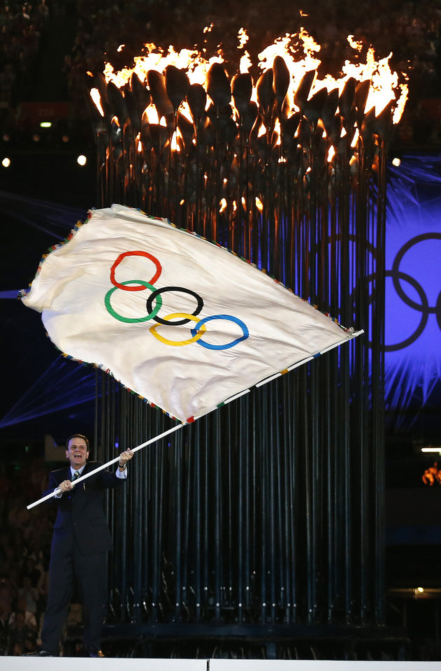 Photo -   The mayor of Rio de Janeiro Eduardo Paes waves the Olympic flag after it was handed to him by President of the International Olympic Committee Jacques Rogge, not seen, during the Closing Ceremony at the 2012 Summer Olympics, Sunday, Aug. 12, 2012, in London. (AP Photo/Matt Dunham)