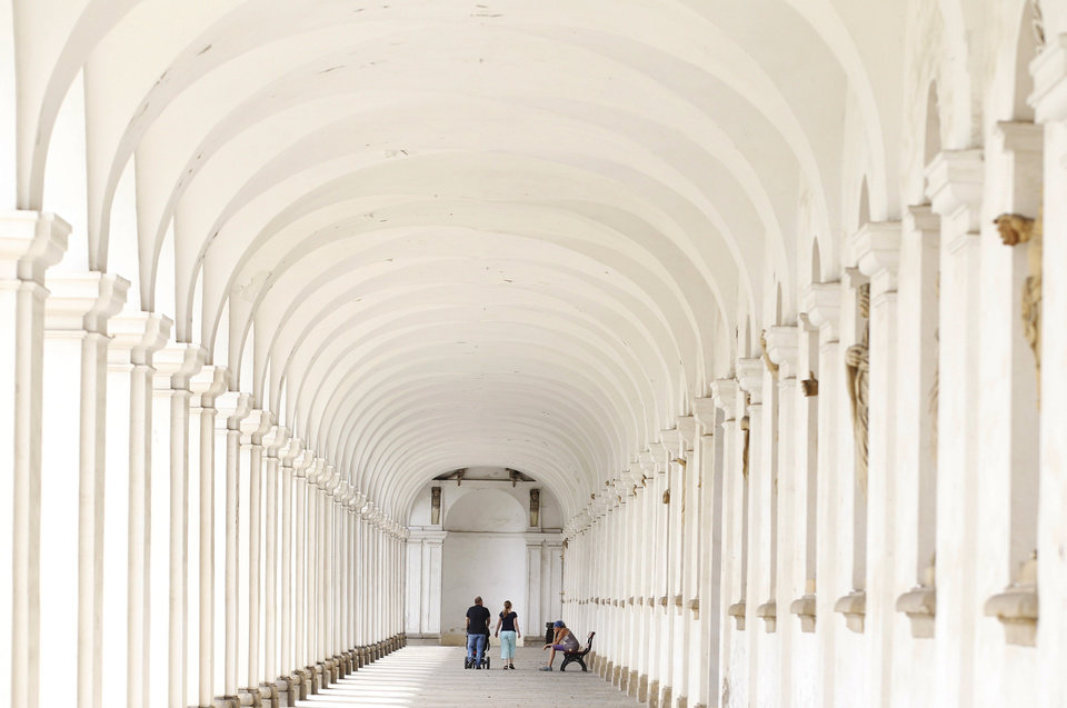 Photo - In this Aug. 7, 2014, photo, tourists walk through the 244-meter long colonnade at UNESCO's Flower Garden in city of Kromeriz, in Czech Republic. The Flower Garden was created on the grounds of an archbishop's castle, but it proved so difficult and expensive to maintain that it was neglected. Ironically, that neglect allowed it to survive for centuries mostly unchanged, though some features disappeared or suffered damage over time. (AP Photo/Petr David Josek)