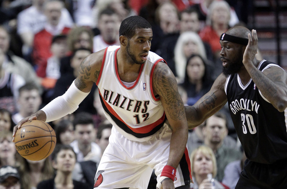 Photo - Portland Trail Blazers forward LaMarcus Aldridge, left, looks to maneuver against Brooklyn Nets forward Reggie Evans during the first quarter of an NBA basketball game in Portland, Ore., Wednesday, March 27, 2013.(AP Photo/Don Ryan)