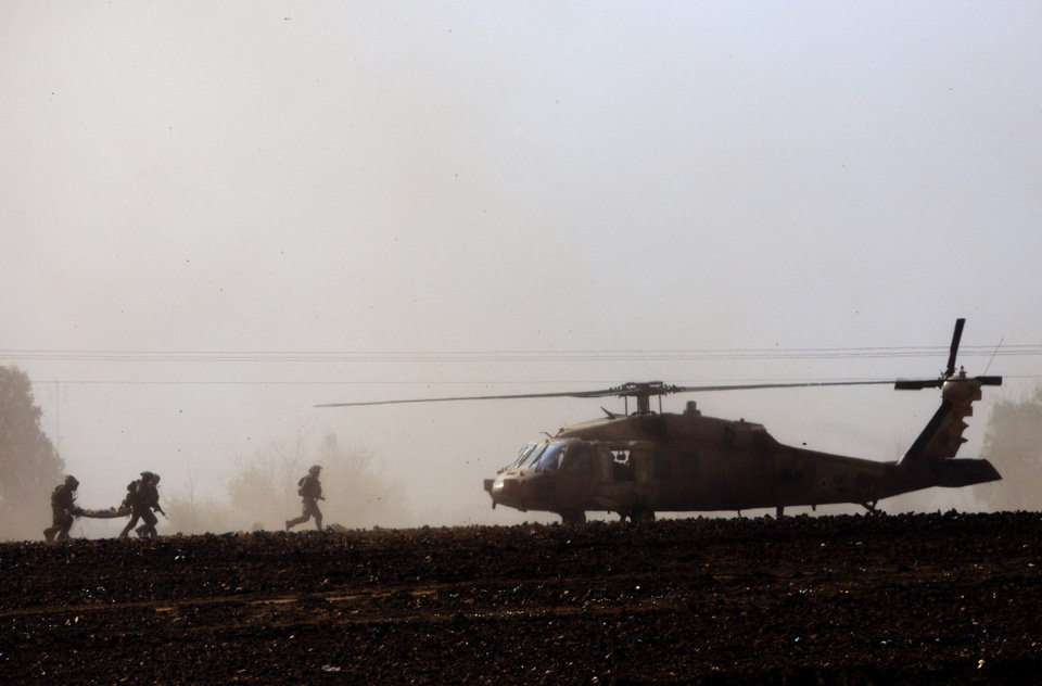 Photo - Israeli soldiers carry wounded soldier to a helicopter near the Israel and Gaza border Thursday, July 24, 2014. Israeli tanks and warplanes bombarded the Gaza Strip on Thursday, as Hamas militants stuck to their demand for the lifting of an Israeli and Egyptian blockade in the face of U.S. efforts to reach a cease-fire. (AP Photo/Dusan Vranic)