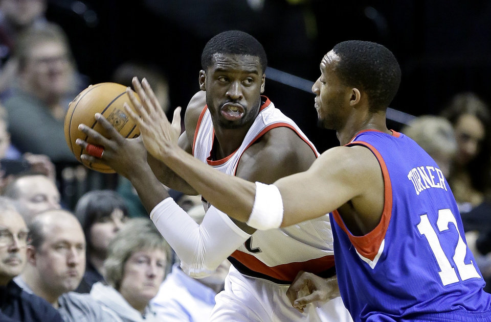 Photo - Portland Trails Blazers guard Wesley Matthews, left, looks to maneuver against Philadelphia 76ers forward Evan Turner during the first half of an NBA basketball game in Portland, Ore., Saturday, Jan. 4, 2014. (AP Photo/Don Ryan)