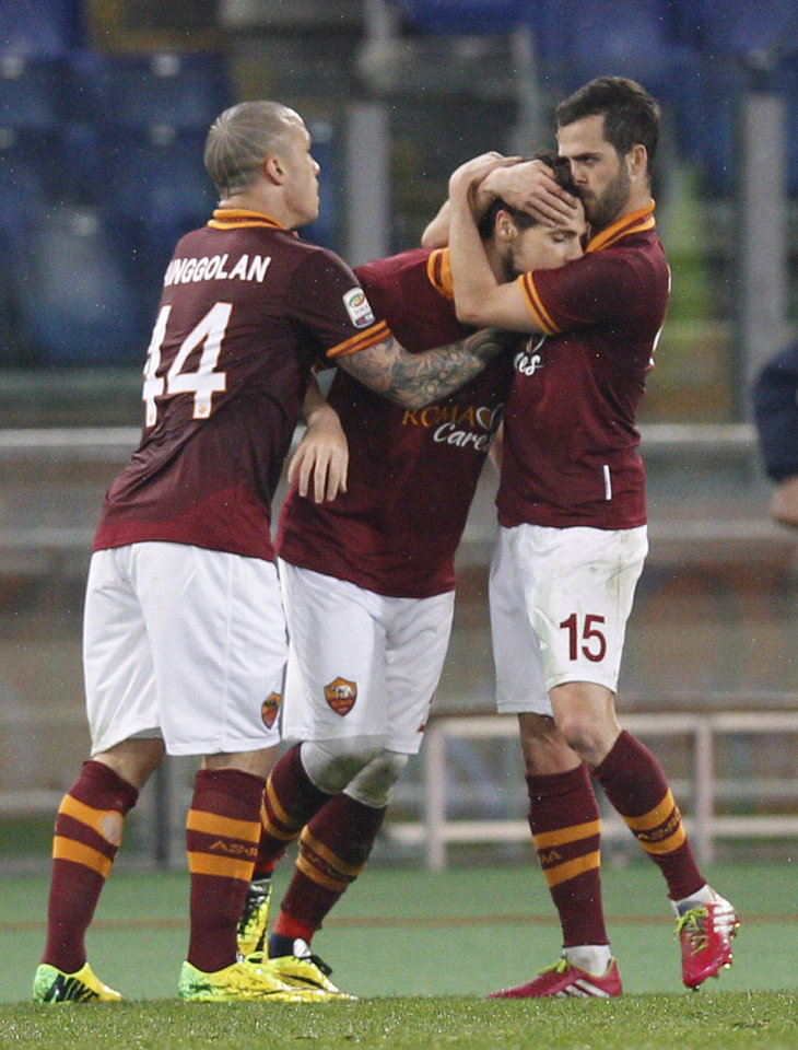 Photo - AS Roma forward Mattia Destro center, is celebrated by his teammates Radja Nainggolan of Belgium, left, and Miralem Pjanic of Bosnia-Erzegovina after he scored during a Serie A soccer match between AS Roma and Torino, at Rome's Olympic Stadium, Tuesday, March 25, 2014. (AP Photo/Andrew Medichini)