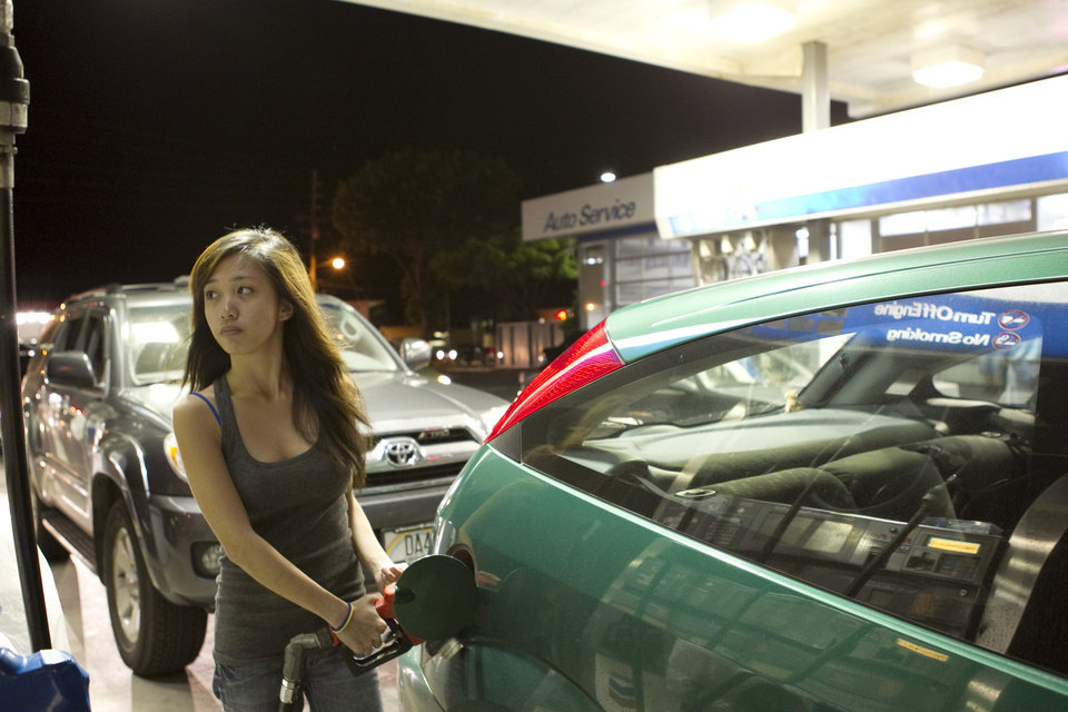 Photo - Ella Marie Lapitan fills her gas tank, Thursday, March 10, 2011 in Ewa, Hawaii as residents brace for a tsunami after a massive earthquake in Japan.  (AP Photo/ Marco Garcia) ORG XMIT: HIMG109