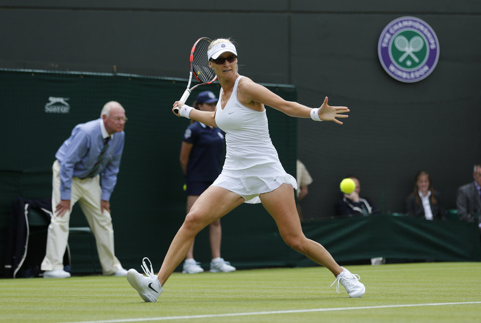 Photo - Mirjana Lucic-Baroni of Croatia returns to Victoria Azarenka of Belarus during their first round match at the All England Lawn Tennis Championships in Wimbledon, London, Monday, June 23, 2014. (AP Photo/Ben Curtis)