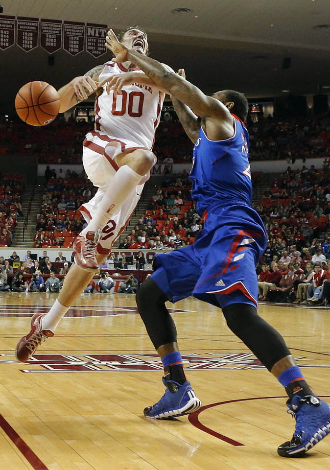 Photo - Oklahoma's Ryan Spangler (00) looses the ball against Kansas' Tarik Black (25) during the NCAA college basketball game between the University of Oklahoma Sooners (OU) and the University of Kansas (KU) Jayhawks at Lloyd Nobel Center in Norman,  Okla. on Wednesday, Jan. 8, 2014.   .Photo by Chris Landsberger, The Oklahoman