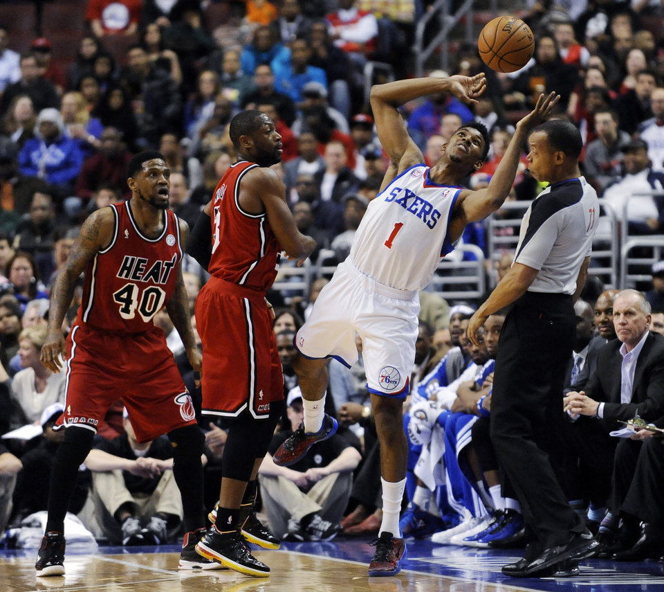 Philadelphia 76ers\' Nick Young (1) reaches up to keep the ball in play in front of Miami Heat\'s Dwyane Wade (3) and Udonis Haslem (40) during the first half of an NBA basketball game, Saturday, Feb. 23, 2013, in Philadelphia. (AP Photo/Michael Perez)