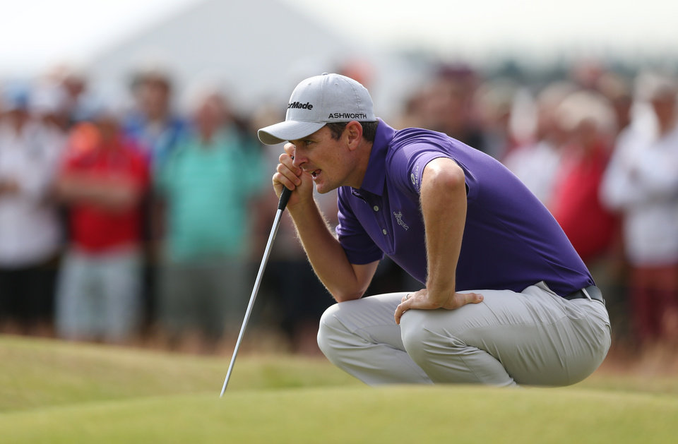 Photo - Justin Rose of England lines up a putt on the 1st green during the second day of the British Open Golf championship at the Royal Liverpool golf club, Hoylake, England, Friday July 18, 2014. (AP Photo/Jon Super)