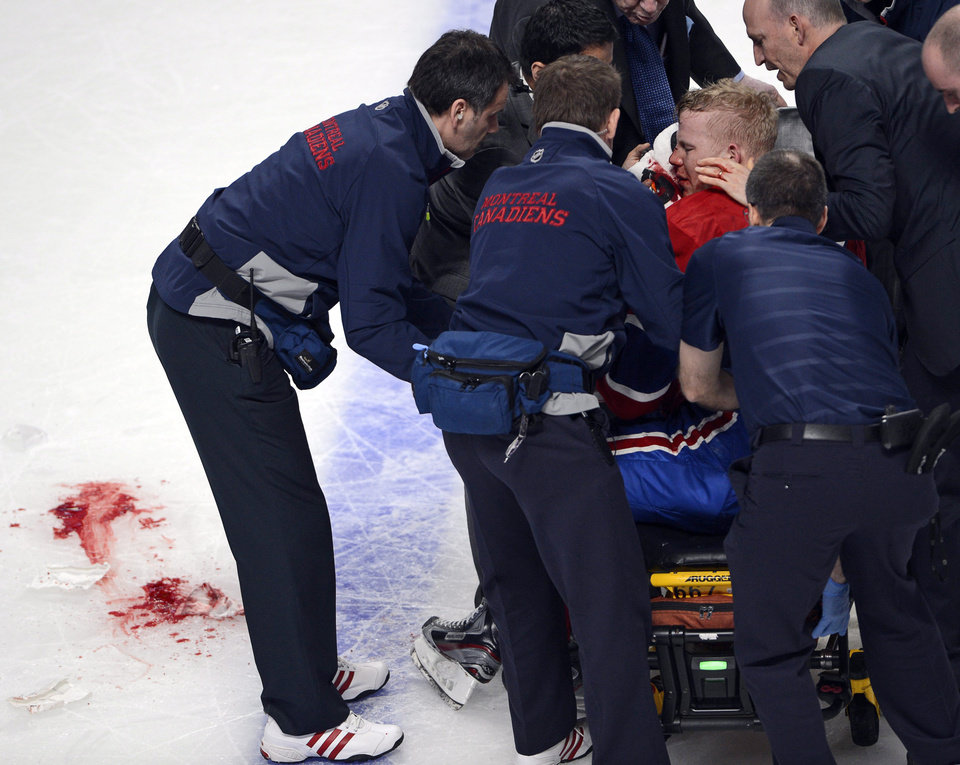 Photo - Montreal Canadiens center Lars Eller is placed on a stretcher after being checked by Ottawa Senators defenseman Eric Gryba during the second period of Game 1 of an NHL hockey Stanley Cup playoffs first-round series in Montreal on Thursday, May 2, 2013. (AP Photo/The Canadian Press, Ryan Remiorz)