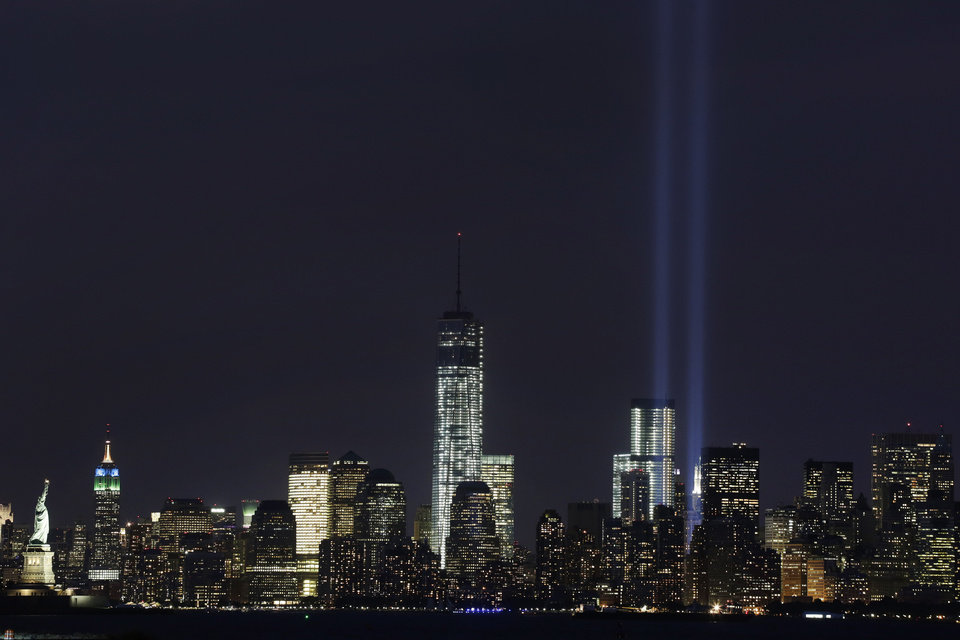 Photo - The Tribute in Light rises above the lower Manhattan skyline and One World Trade Center, center, in a test of the memorial light display, Monday, Sept. 9, 2013 in New York. The twin beams of light will also appear Wednesday, Sept. 11, twelve years after the terrorist attacks of Sept. 11, 2001. The Statue of Liberty and Empire State Building are at far left. (AP Photo/Mark Lennihan)